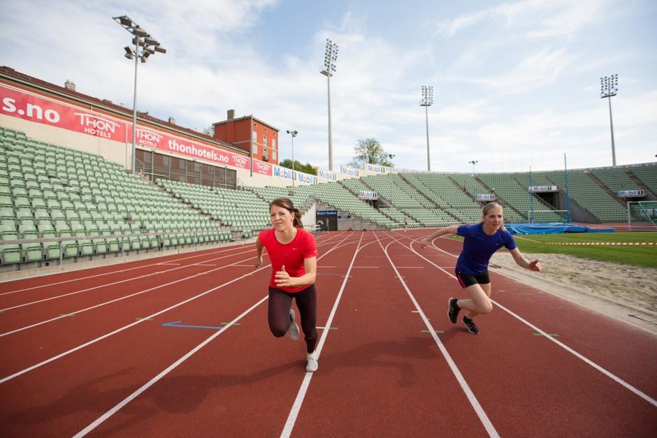 To kvinner løper mot kamera på løpebanen inne på Bislett Stadion.