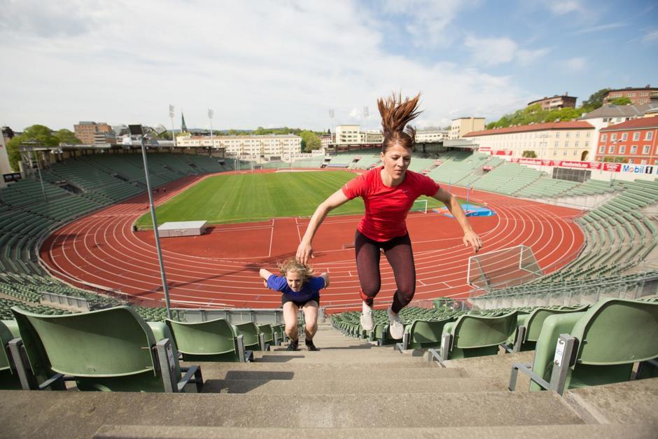To kvinner hopper opp trappene på tribunen inne på Bislett stadion.