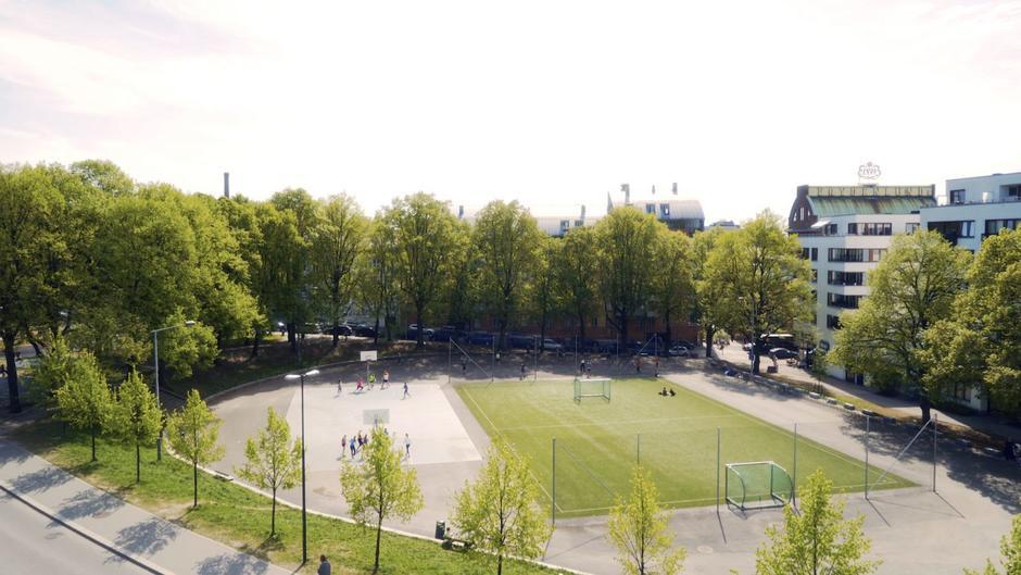 Oversiktsbilde over fotballbanen til høyre og basketballbanen til venstre omringet av trær og blokker