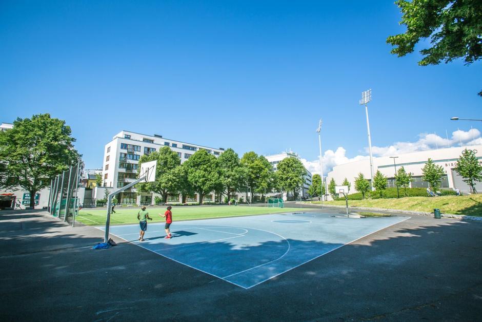 To menn spiller basketball på banen i solen