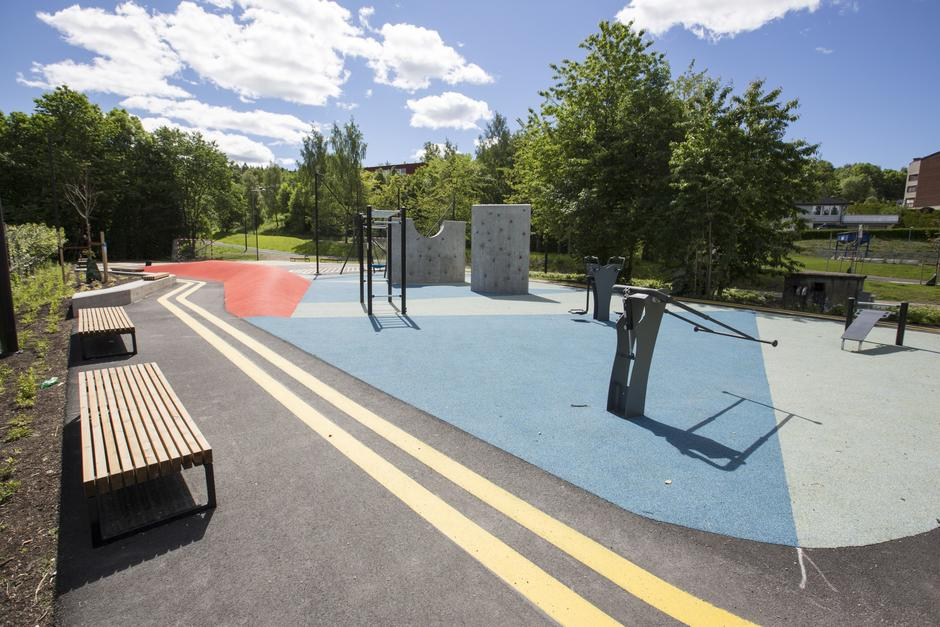 Park med sittebenker, treningsapparater og buldrevegg
