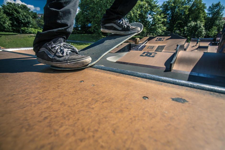 Detaljbilde av skateboard med skateanlegget i bakgrunnen