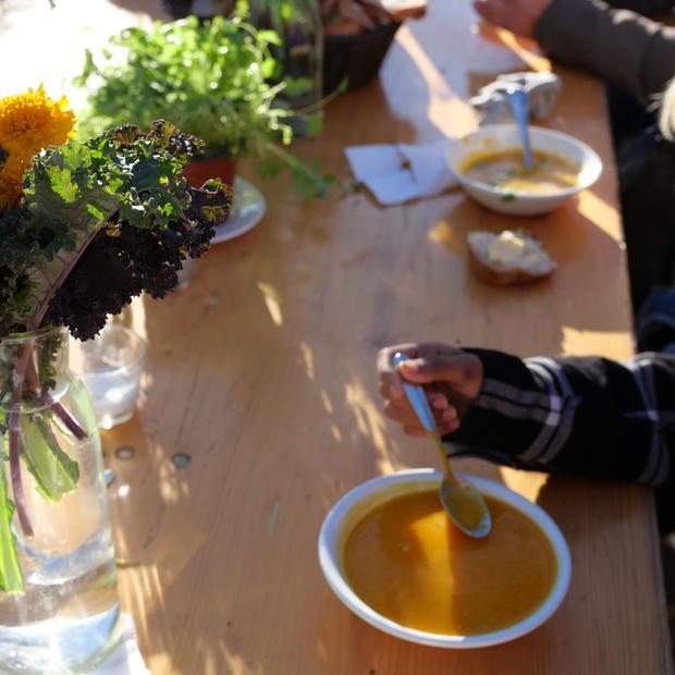 Et bord med suppetallerken og en bukett med høstfarger