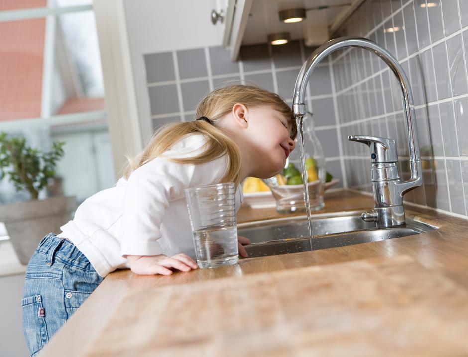 Jente drikker vann av springen.