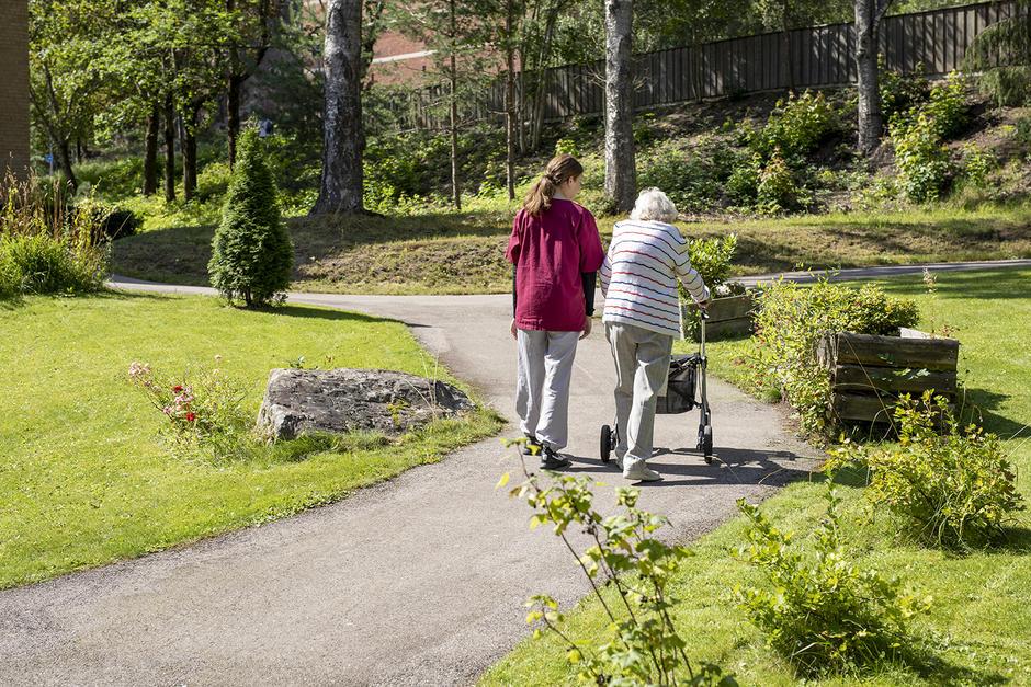 Sommerbilde hvor aktivitør og beboer med gåstol går en tur