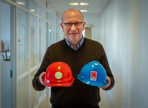 Direktør Hans Petter Karlsen holder en rød og en blå hjelm.