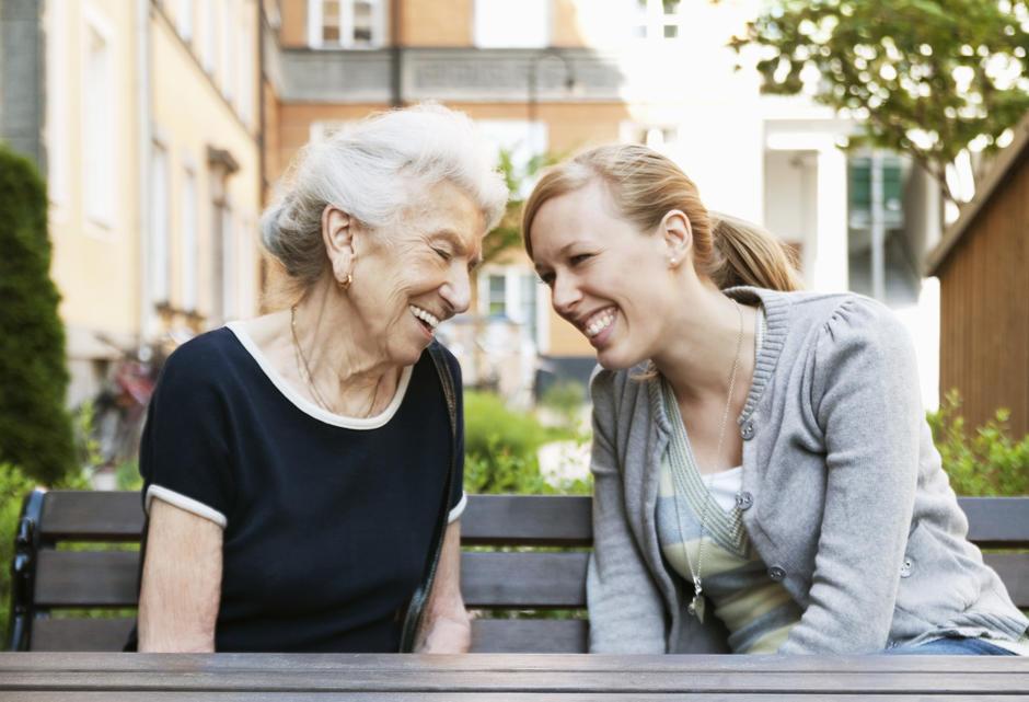 Eldre og ung kvinne sitter ute på en benk og koser seg.