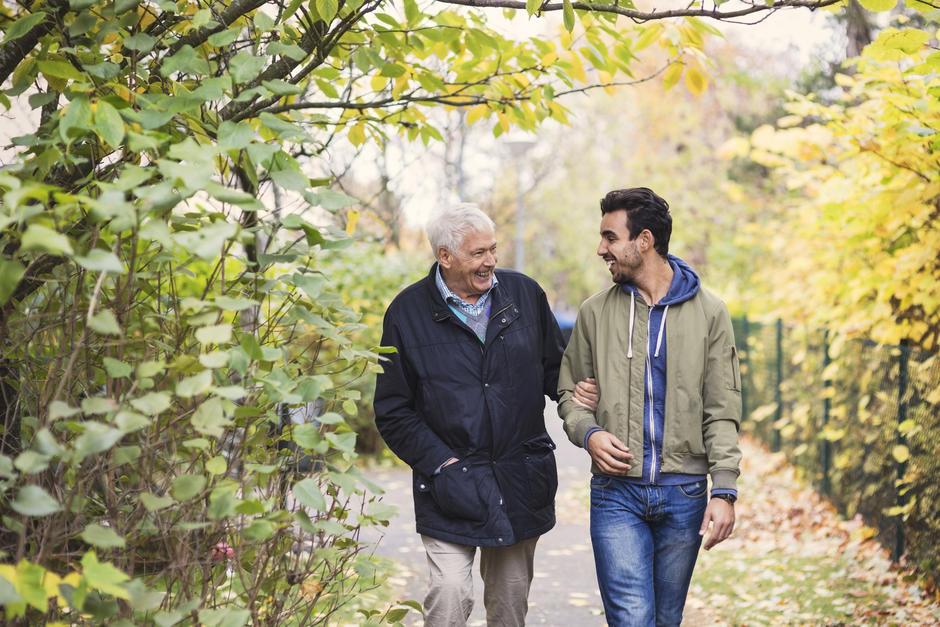 Eldre mann går tur med en yngre mann.