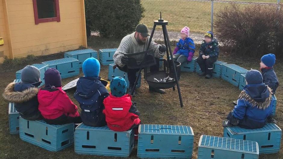 Mann står ved en bålpanne ute i høstværet, barna sitter rundt bålet.