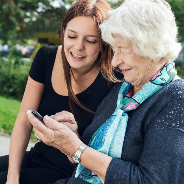 Bildet viser en eldre kvinne med telefon.