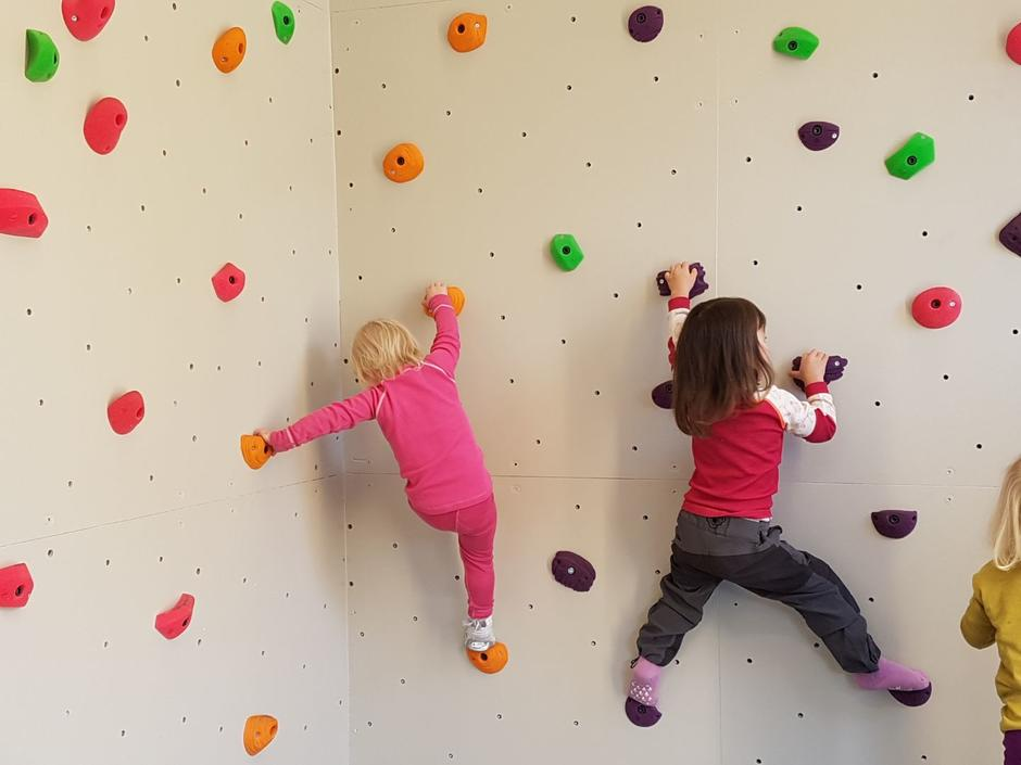 To barn klatrer opp en hvit klatrevegg.