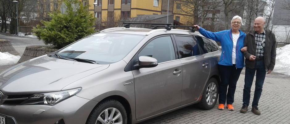To personer står ved bilen til seniorsenteret.