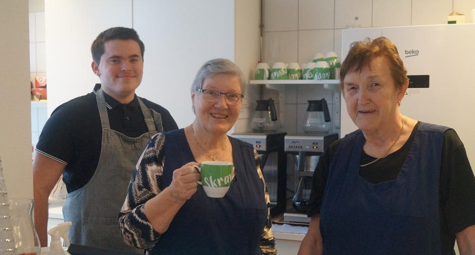 Tre frivillige smiler mot kamera.