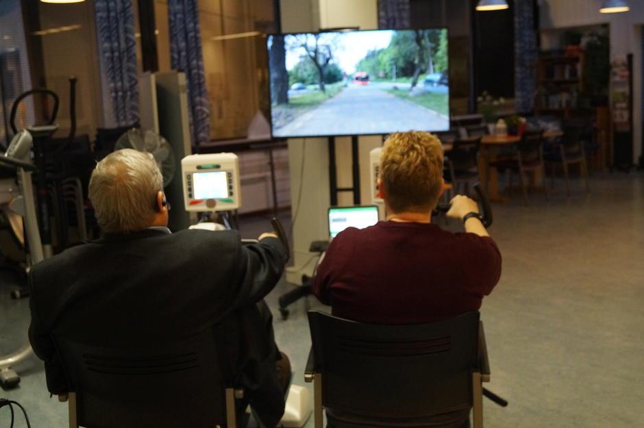 To personer sykler med en skjerm foran seg med video av Oslos gater