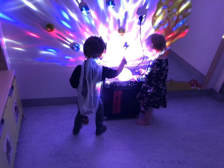 barn står ved høyttaler med discokule i mørkt rom.