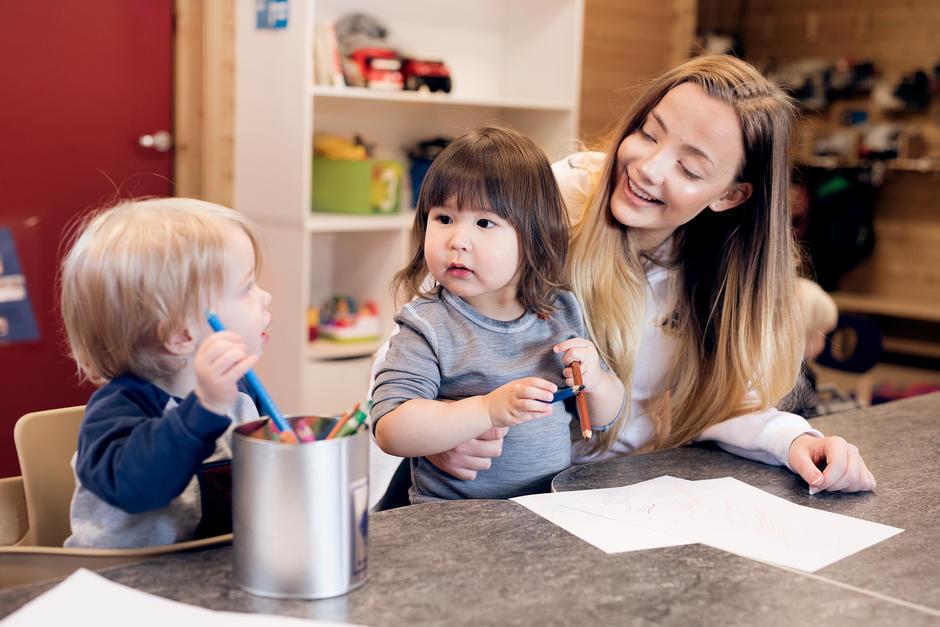 To barn tegner og en voksen i barnehagen har god kontakt med begge barna