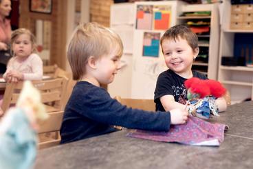 To barn sitter ved et bord og leker med figurer de har laget selv.