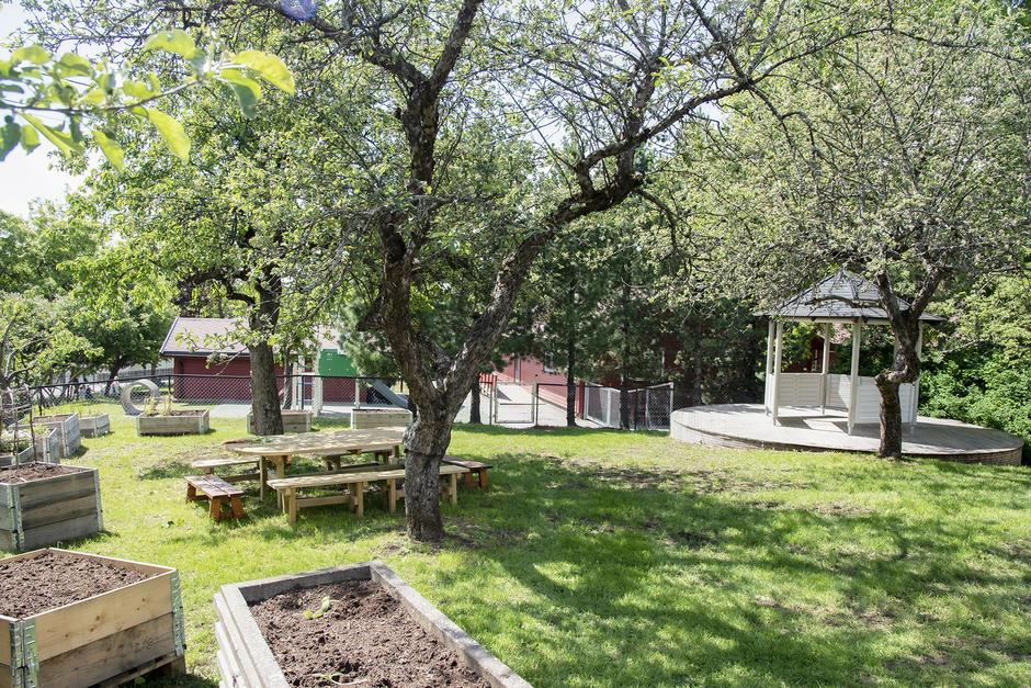 Kjøkkenhage med plantekasser, sittemøbler, paviljong, frukt og epletrær med port inn til Borgenveien barnehage