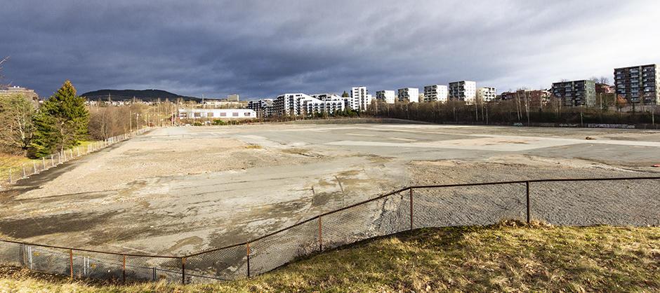 """Asfaltert tomt (""""Økern torg"""") sett mot bebyggelse i nord."""