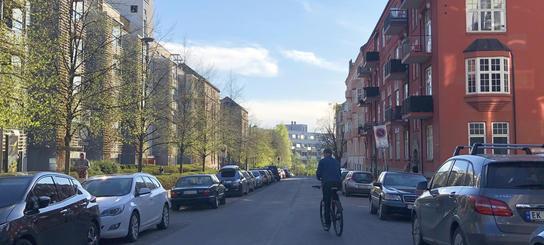 Fotografi av Stensberggata før tilrettelegging. Det er biler parkert langs begge sider av veien og en syklist sykler midt i gaten.
