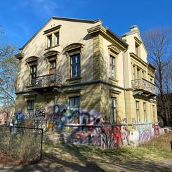 Lysegult murhus, med balkonger tagging nederst på fasaden