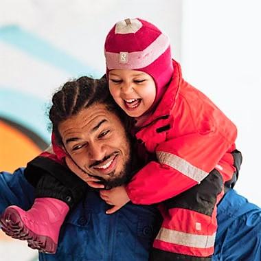 Barnehageansatt med barn på skuldrene