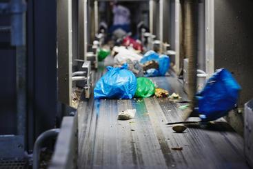 Avfallsposer på sorteringsbånd.
