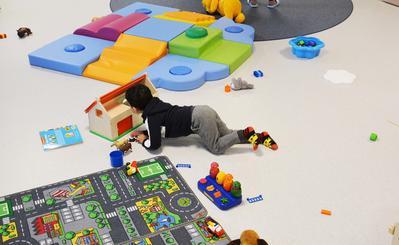 Gutt sett bakfra ligger på gulvet og leker. Leketeppe og mange fargerike leker utover gulvet.
