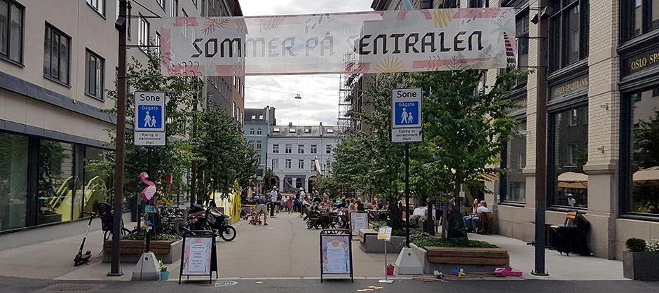 """Gåate med trær og benker på begge sider. Banner med påskriften """"sommer på sentralen"""" mellom to stolper."""