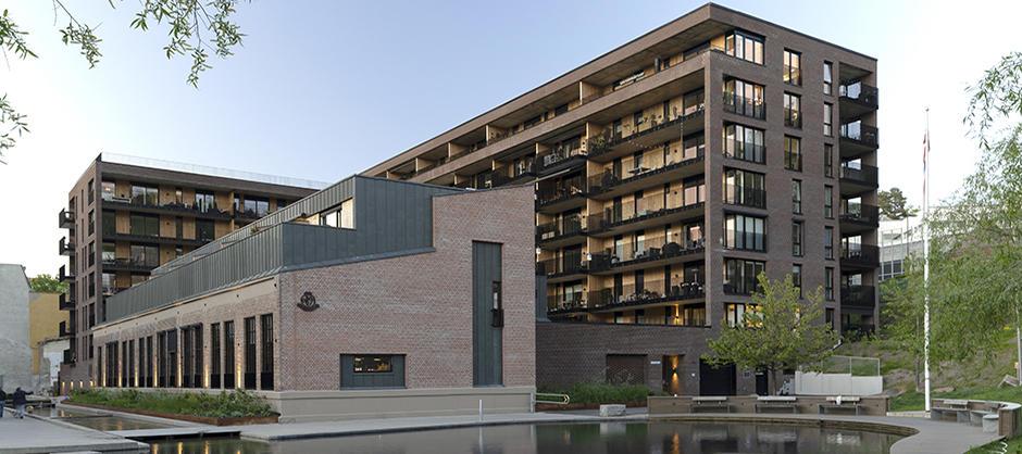 Teglsteinblokk i sju etasjer, med lavere blokk foran. Vannspeil i front.