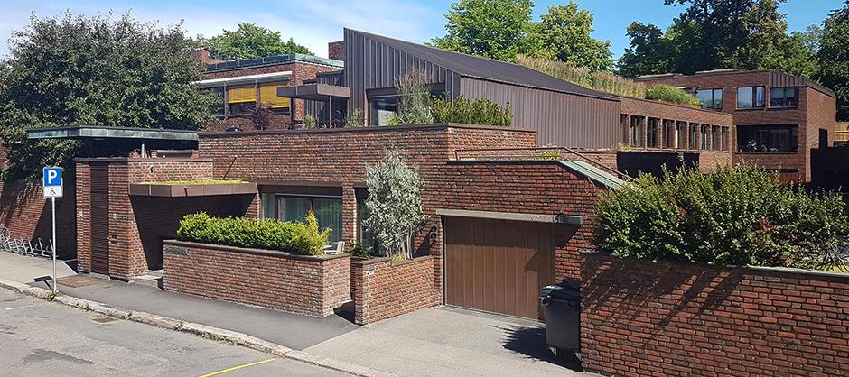Boligbygg i tre og teglstein, med garasjeport