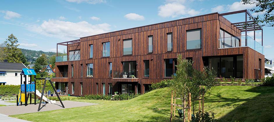 Bygg på tre etasjer i tre. Høye vinduer og terrasse med glassgjerde og overbygg.