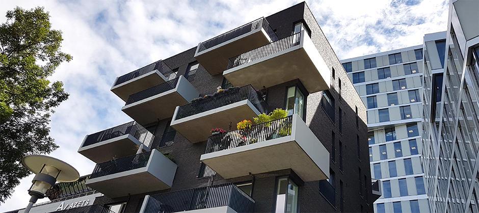 Froskefoto av steinbygg. Store balkonger som stikker langt ut fra bygget.