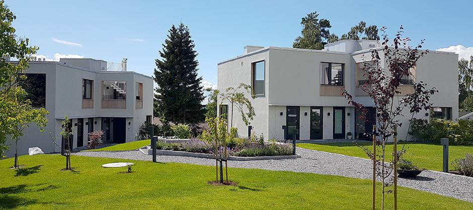 To hvite boligbygg med flatt tak på et tun.