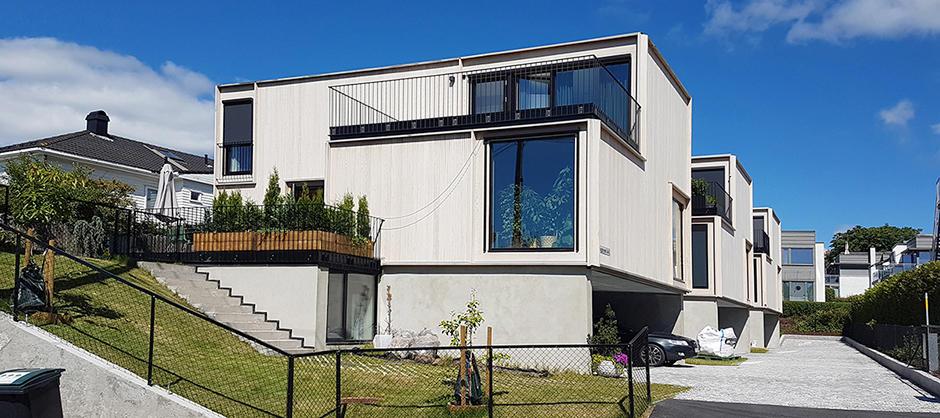 Toetasjes bygg med terrasse i andre etasje.