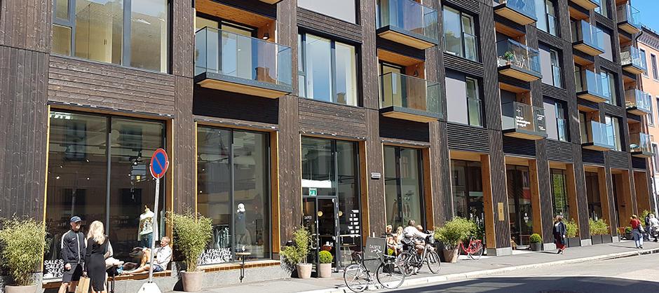 Blokk i bysentrum, næringslokaler med store vindusflater i første etasje, glassbalkonger i etasjene oppover