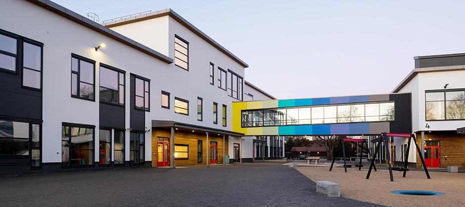 To hvite skolebygg med en fargerik lukket bru mellom