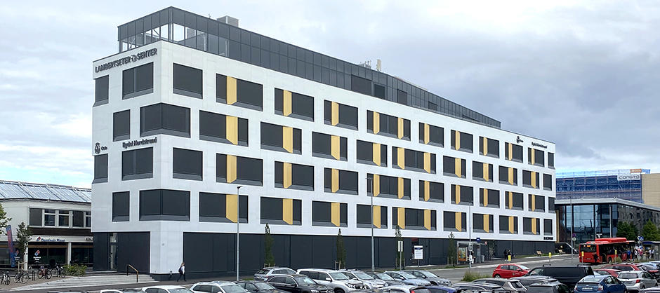 Seksetasjes hvitt kontorbygg, hvor den øverste etasjen er litt lenger inn enn de andre.