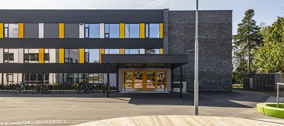 Treetasjes bygg i grå stein, med gule og lysegrå felter mellom vinduene.