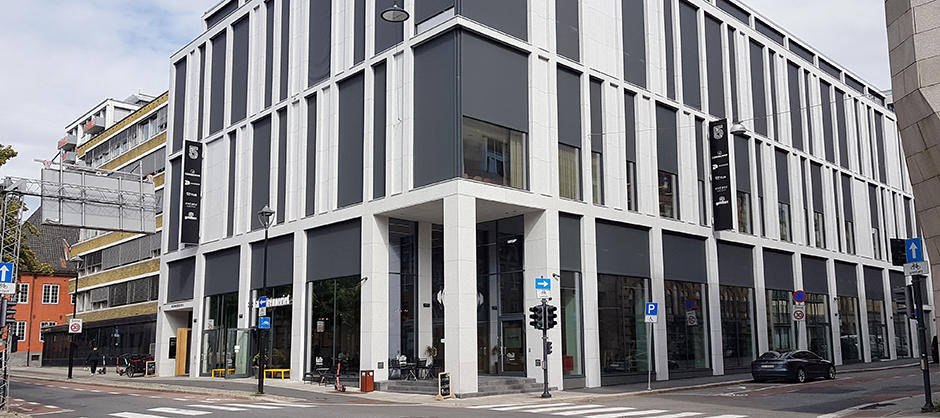 Treetasjes kontorbygg med store vindusflater, og struktur i fasaden. Andre etasje stikker ut over næringslokalene i første etasje.