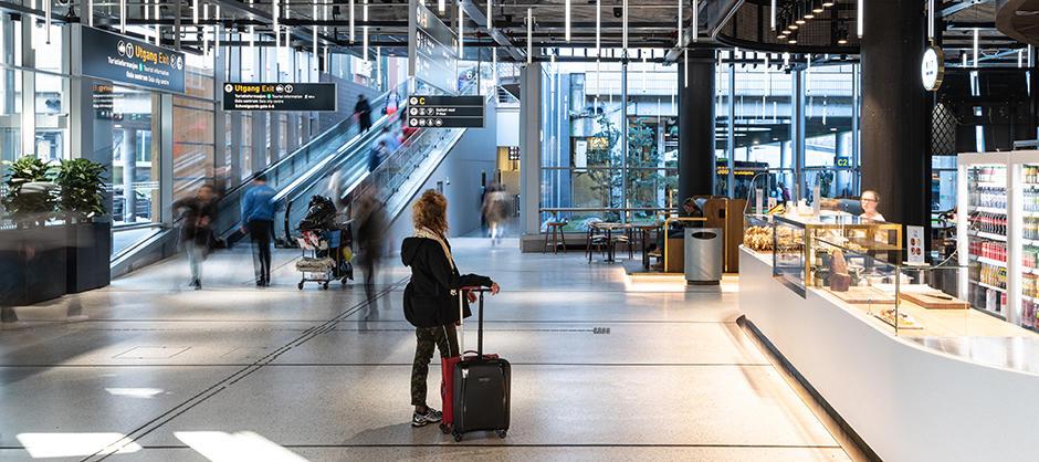 """Interiør på Oslo bussterminal, med """"avgangshall"""". Lys i taket, og serveringsdisk til høyre."""