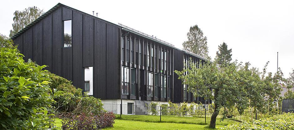 Hus i grønn hage. Smalt panel og skråtak. To høye vinduer på kortsiden, tette vinduer på langsiden.