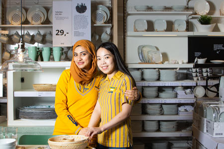 Truc Tang og Noreen Khan i ikeauniformer, foran tallerkenhylle