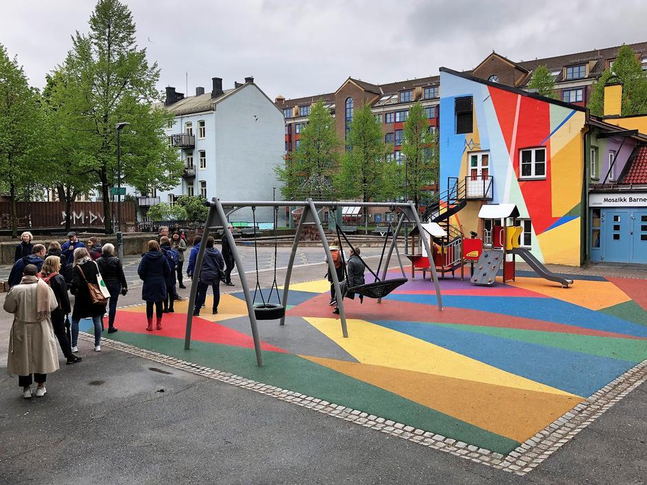 Gruppe mennesker med ryggen til i Urtehagen på Grønland. Fargerike bygg og lekestativ.