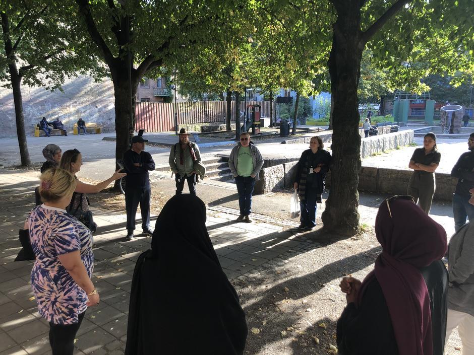 En gruppe mennesker står i en ring med god avstand under trær.