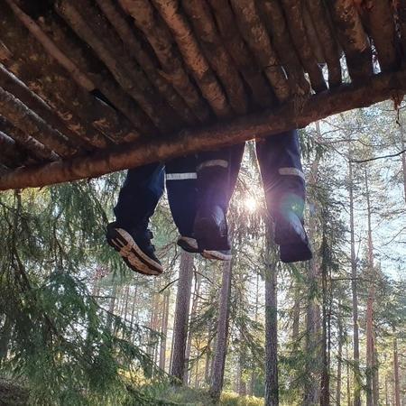 Barn som sitter på en trekonstruksjon i skogen. Det er bare beina og trærne i bakgrunnen som vises.