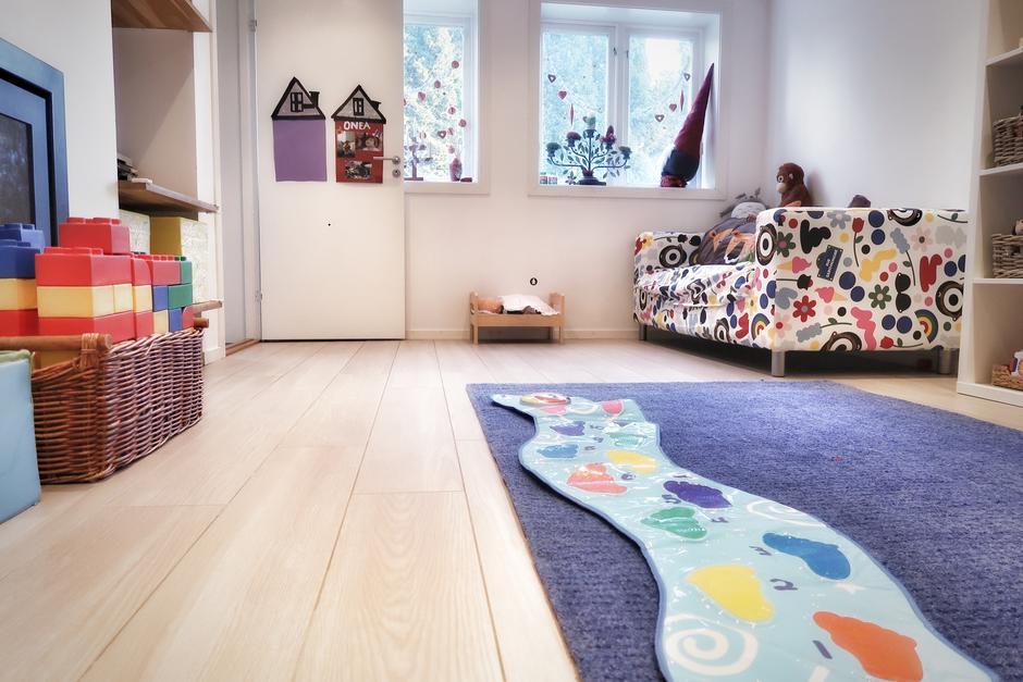 Innendørs, en fargerik sofa, mønstrete teppe på gulvet og leker i hyller langs veggene.