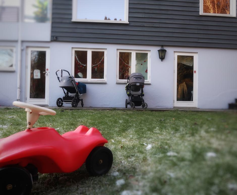 Husvegg med gressplen foran. Barnevogner stilt opp langs husveggen.