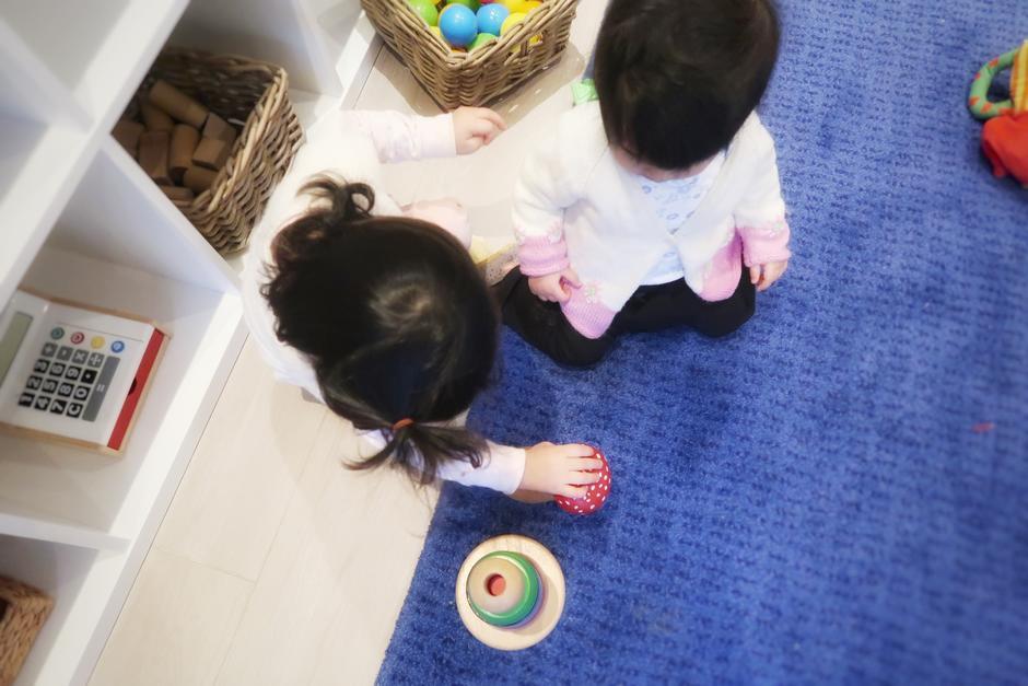 Barn fotografert ovenfra mens de leker på et blått teppe.