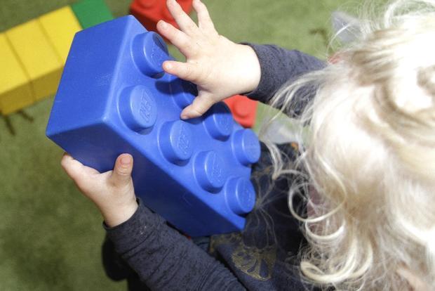 Barn holder stor legokloss-leke.